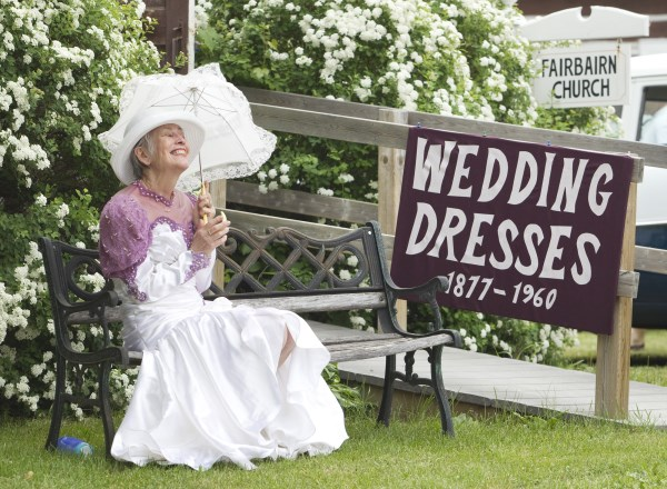 Woman holding an umbrella beside a wedding dresses sign at Kawartha Settlers Village