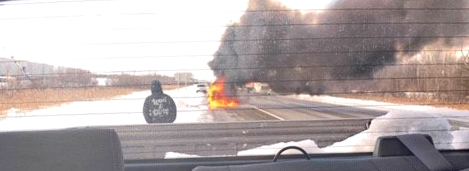 A vehicle is seen in flames on Highway 417, shortly after an off duty firefighter helped the two occupants escape.