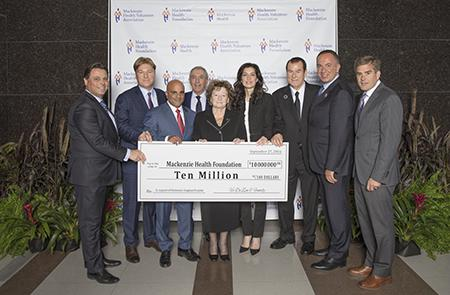 Vic De Zen family and guests handing over large print check