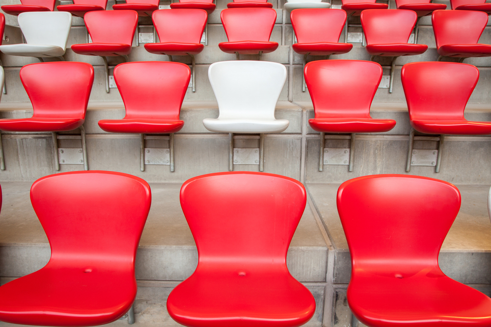 White chair surrounded by red chairs
